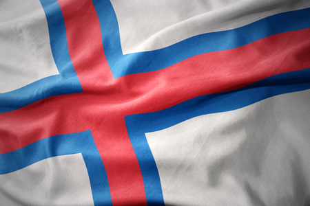 waving colorful national flag of faroe islands. Stock Photo