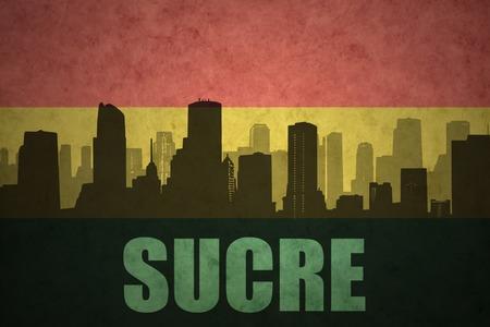 bolivian: abstract silhouette of the city with text Sucre at the vintage bolivian flag background