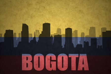 colombian flag: abstract silhouette of the city with text Bogota at the vintage colombian flag background