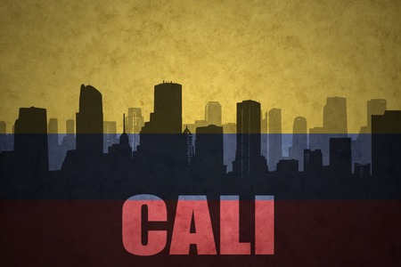 colombian flag: abstract silhouette of the city with text Cali at the vintage colombian flag background