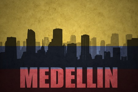 colombian flag: abstract silhouette of the city with text Medellin at the vintage colombian flag background