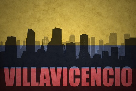 colombian flag: abstract silhouette of the city with text Villavicencio at the vintage colombian flag background