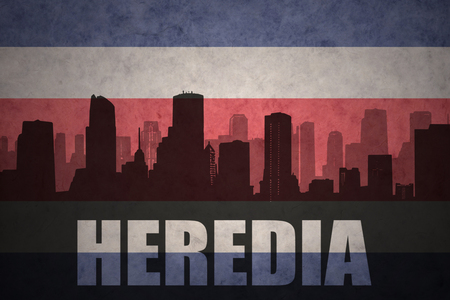 clash: abstract silhouette of the city with text Heredia at the vintage costa rican flag background
