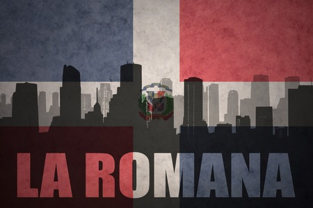 clash: abstract silhouette of the city with text La Romana at the vintage dominican republic flag background