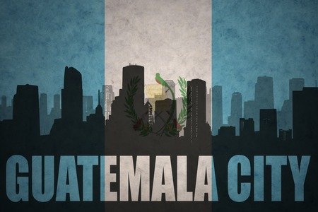 guatemalan: abstract silhouette of the city with text Guatemala City at the vintage guatemalan flag background