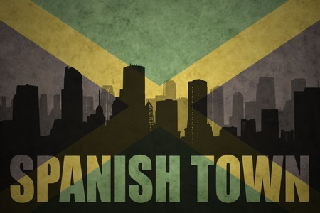 clash: abstract silhouette of the city with text Spanish Town at the vintage jamaican flag background