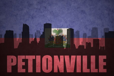 clash: abstract silhouette of the city with text Petionville at the vintage haitian flag background