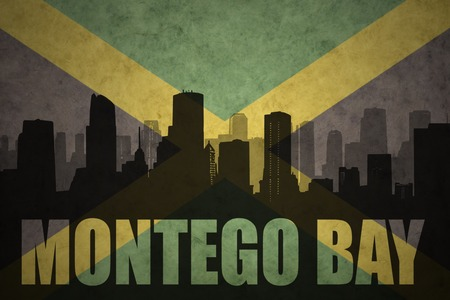 jamaican: abstract silhouette of the city with text Montego Bay at the vintage jamaican flag background