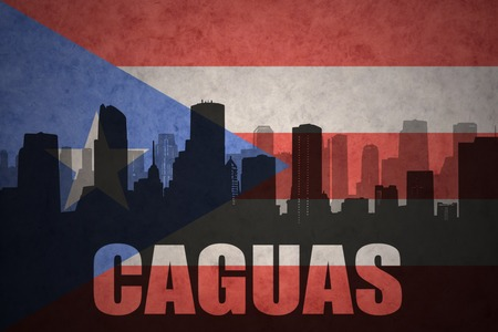 clash: abstract silhouette of the city with text Caguas at the vintage puerto rican flag background