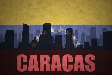 venezuelan flag: abstract silhouette of the city with text Caracas at the vintage venezuelan flag background