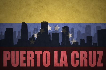venezuelan flag: abstract silhouette of the city with text Puerto La Cruz at the vintage venezuelan flag background Stock Photo