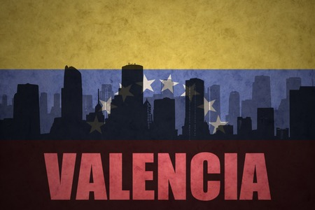 venezuelan flag: abstract silhouette of the city with text Valencia at the vintage venezuelan flag background