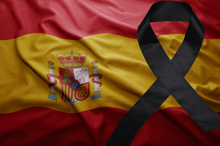 waving national flag of spain with black mourning ribbon