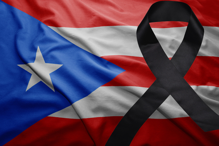 waving national flag of puerto rico with black mourning ribbon