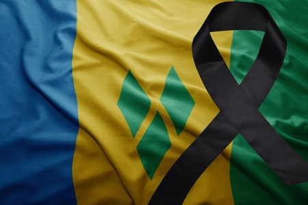 waving national flag of saint vincent and the grenadines with black mourning ribbon Stock Photo