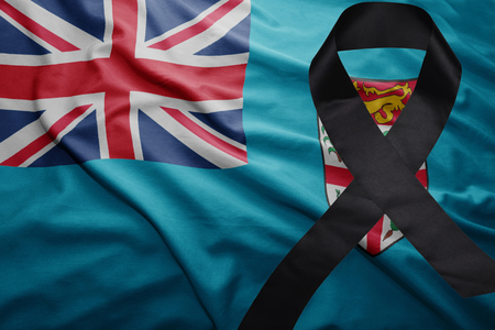 conflictos sociales: waving national flag of Fiji with black mourning ribbon