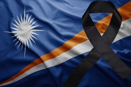 waving national flag of Marshall Islands with black mourning ribbon