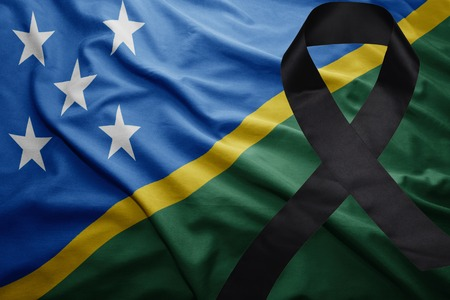 waving national flag of Solomon Islands with black mourning ribbon