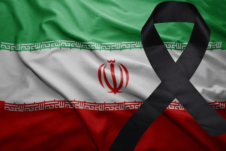 waving national flag of iran with black mourning ribbon Stock Photo