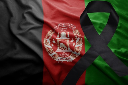 waving national flag of afghanistan with black mourning ribbon Stock Photo