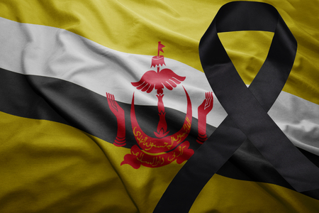 waving national flag of brunei with black mourning ribbon