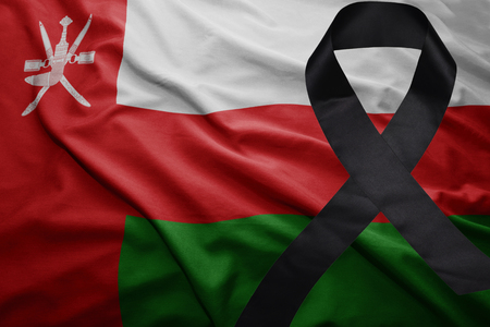 waving national flag of oman with black mourning ribbon