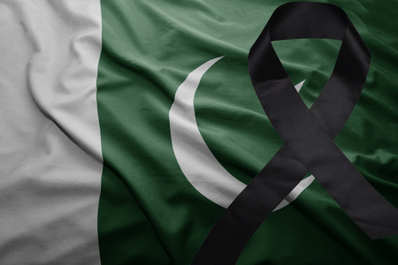 waving national flag of pakistan with black mourning ribbon