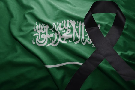 waving national flag of saudi arabia with black mourning ribbon