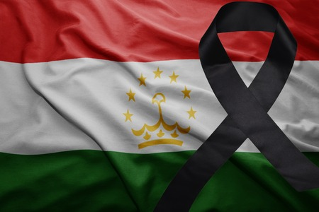 waving national flag of tajikistan with black mourning ribbon