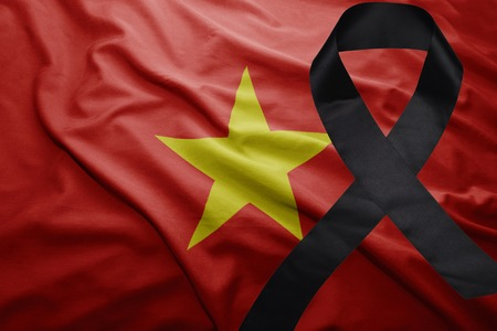 waving national flag of vietnam with black mourning ribbon