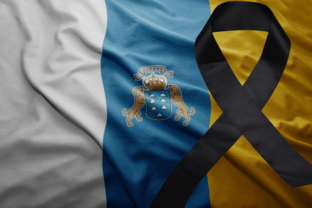 conflictos sociales: waving national flag of canary islands with black mourning ribbon