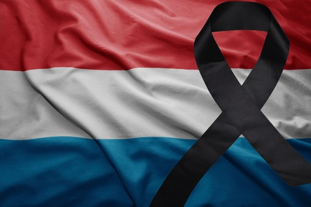 waving national flag of luxembourg with black mourning ribbon Stock Photo