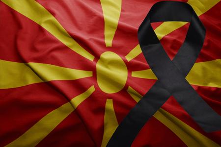 waving national flag of macedonia with black mourning ribbon
