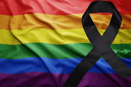 waving gay rainbow flag with black mourning ribbon Stock Photo