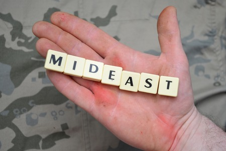 mideast: letters with text mideast on a dirty hand. on the khaki background. concept