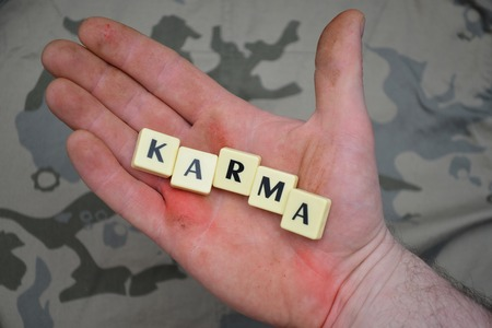 karma: letters with text karma on a dirty hand. on the khaki background. concept