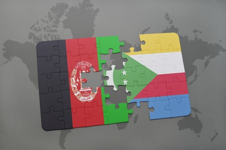 middle east conflict: puzzle with the national flag of afghanistan and comoros on a world map background. 3D illustration
