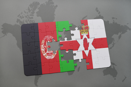 middle east conflict: puzzle with the national flag of afghanistan and northern ireland on a world map background. 3D illustration Stock Photo