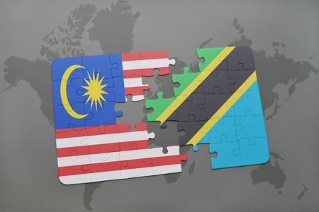 puzzle with the national flag of malaysia and tanzania on a world map background. 3D illustration