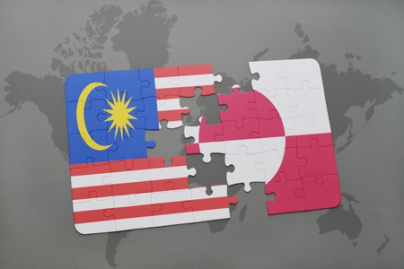 danish flag: puzzle with the national flag of malaysia and greenland on a world map background. 3D illustration Stock Photo