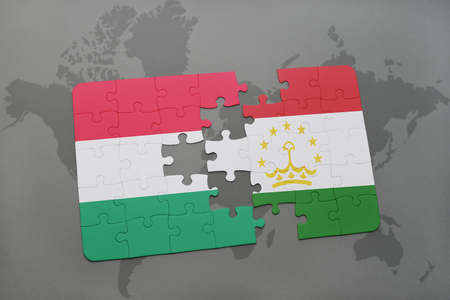 economy of tajikistan: puzzle with the national flag of hungary and tajikistan on a world map background. 3D illustration