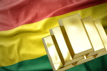reservas de oro. brillantes lingotes de oro en el fondo de la bandera de bolivia Foto de archivo