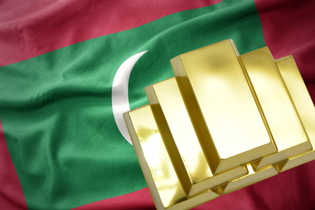 concern: gold reserves. shining golden bullions on the maldives flag background