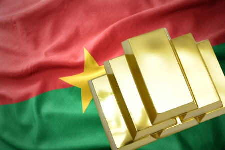 gold reserves. shining golden bullions on the burkina faso flag background