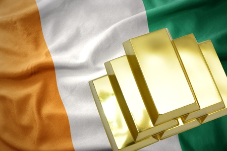 gold reserves. shining golden bullions on the cote divoire flag background