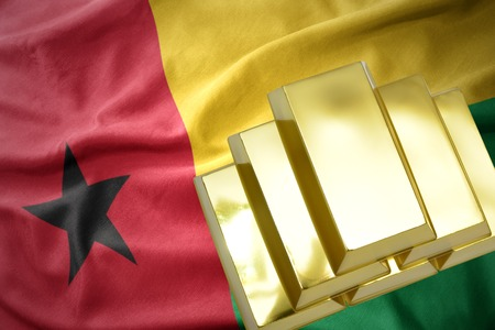 gold reserves. shining golden bullions on the guinea bissau flag background