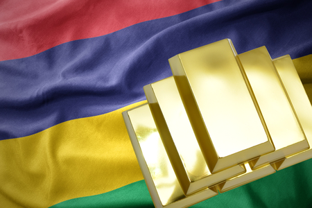 gold reserves. shining golden bullions on the mauritius flag background