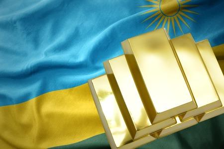 gold reserves. shining golden bullions on the rwanda flag background Stock Photo