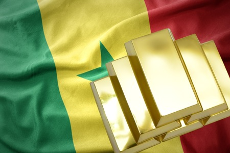 gold reserves. shining golden bullions on the senegal flag background Stock Photo
