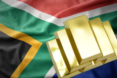 gold reserves. shining golden bullions on the south africa flag background Stock Photo